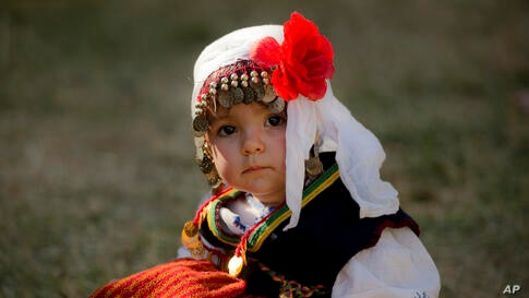 Kristina, a 2 year-old Bulgarian girl wearing a traditional outfit, sits on the grass during a wedding in Pchelina, Bulgaria, July 6, 2014.
