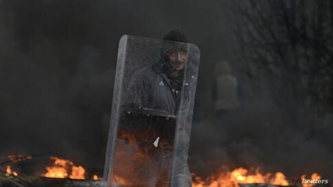 A pro-Russian protester holds a shield at a check point, with black smoke from burning tires rising above, in Slaviansk. Ukraine's Interior Minister on Sunday urged residents in the eastern city of Slaviansk to stay indoors.