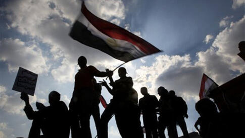 Anti-government protesters hold an Egyptian flag during demonstrations in Tahrir Square in downtown Cairo, Egypt Tuesday, Feb. 8, 2011.