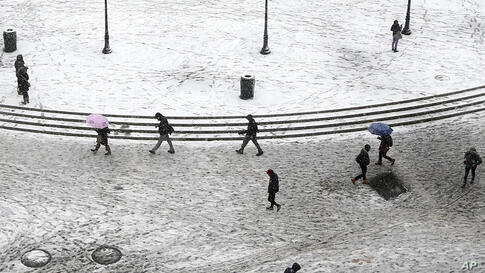 Pedestrians trudge through dirty snow and slush as they pass through Union Square in New York. Another winter storm bears down on the eastern U.S., only a day after temperatures soared into the 50s (F).