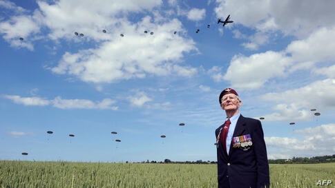 British World War II veteran Frederick Glover looks at soldiers parachuting down during a D-Day commemoration paratroopers launch event in Ranville, northern France, on the eve of the 70th anniversary of the World War II Allied landings in Normandy.