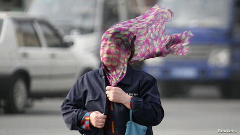 A strong wind blows a scraf in a woman's face as she crosses a street in Shenyang, Liaoning province, China.