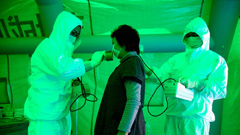 Medical staff use a Geiger counter to screen a woman for radiation exposure after she evacuated from an area within 20km (12.4 miles) radius of the Fukushima Daiichi nuclear plant. (Reuters)
