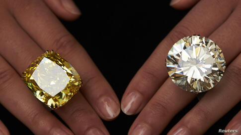 A model poses with a vivid yellow 100.09 carat diamond (L) and a 103.46 carat diamond ring during an auction preview at Sotheby's in Geneva, Switzerland. These items are expected to reach between $15,000,000 to 25,000,000 and $3,500,00 to 5,000,000 whe...