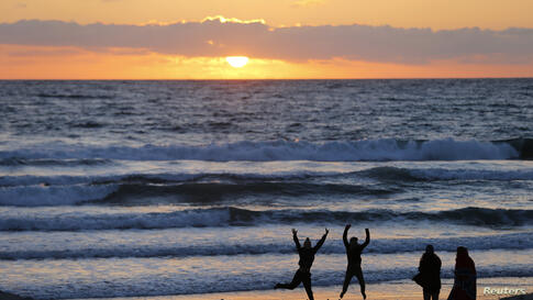 Teenagers pose while having their pictures taken with a phone as the sun sets in Encinitas, California, USA, Mar. 31, 2014.