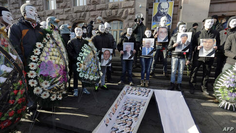 People wearing Guy Fawkes masks hold pictures of pro-presidential Regions' Party parliament members during a symbolic funeral in the centre of Kyiv, Ukraine.