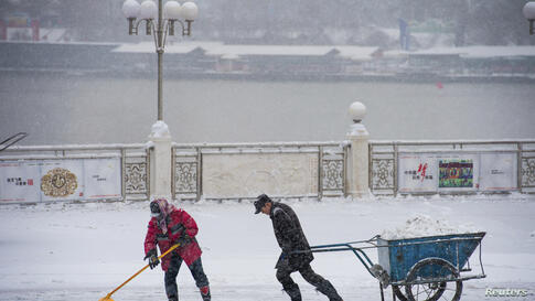 A cleaner pulls a cart as another shovels ice during heavy snow on a street in Jilin, Jilin province, China.