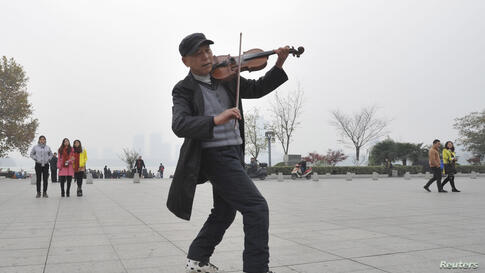 A man plays violin as he roller-skates on a sqauare on a hazy day in Nanjing, Jiangsu province, China.