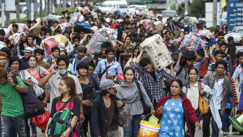 Cambodian migrant workers carry their belongings as they cross the border at Aranyaprathet in Sa Kaew, Thailand, as the military that seized power in a May 22 coup intensifies lax measures to regulate illegal labor.