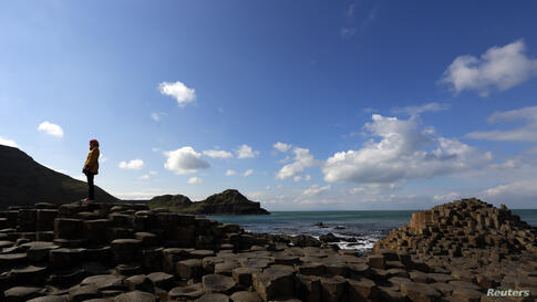 A woman stands on the rocks at the Giant's Causeway situated on the north coast of Northern Ireland.