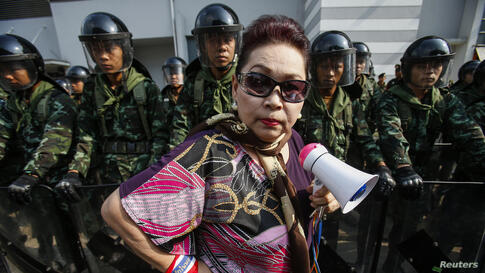 An anti-government protester stands near Thai soldiers guarding the Defence Ministry compound, which is serving as a temporary office for Thai Prime Minister Yingluck Shinawatra, in north Bangkok,