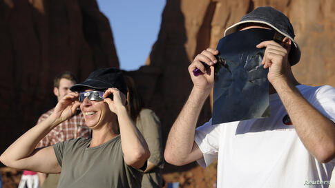 Tourists look through solar eclipse glasses and solar viewers during an annular eclipse in Monument Valley Tribal Park in Utah, May 20, 2012.