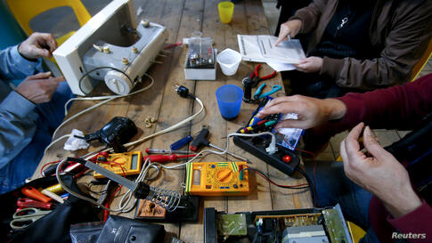People work on non-functioning electrical items at a so-called 'Repair Cafe' in Berlin's Kreuzberg district, Germany.