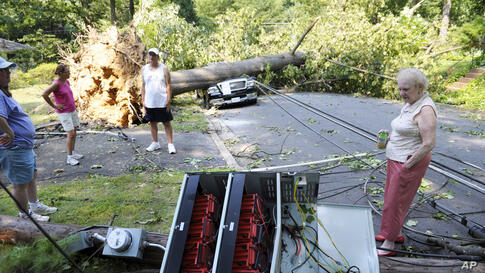 Marilyn Golias, right, looks at the remains of a utility pole which fell across the street from her house in Falls Church, Va., June 30, 2012.