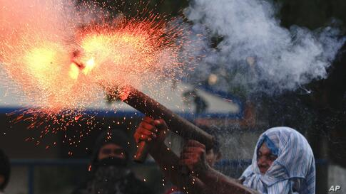 A relative of the former worker of the Ingenio San Antonio fires a homemade mortar during protests in Chichigalpa, Nicaragua, Jan. 19, 2014. The former sugarcane cutters were demanding compensation for damages to their health resulting from alleged exp...