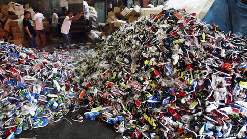 Government workers from the Bureau of Customs destroy counterfeit footwear products in Manila, the Philippines. A government statement said over 150,000 pairs of fake shoes and slippers of various brands including Nike, Adidas, Converse, Sketchers, Nor...