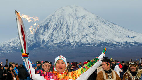 A handout picture taken during the Sochi 2014 Winter Olympic torch relay on Nov. 12, 2013, and released by the Sochi 2014 Winter Olympics Organizing Committee shows a torchbearer rising her torch at Russia's Pacific Kamchatka peninsula, some 6766 kilom...