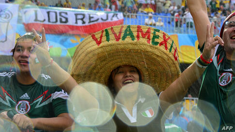 Mexican football fans cheer for their team during the Group A football match between Mexico and Cameroon at the Dunas Arena in Natal, Brazil, during the 2014 FIFA World Cup.