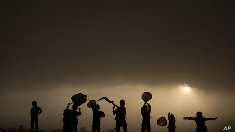 Afghan refugee children play with plastic bags as kites as the sun sets on the outskirts of Islamabad, Pakistan.