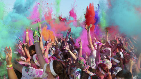 People throw colored powder in the air at the Color Run in Sydney, Australia. The event is a 5-km (3.1-mile) fun run where participants are covered with bright-colored powder at each check station and is less about speed and more about enjoying a day ...