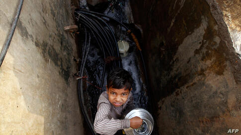 An Indian boy holds a pot after collecting water n a slum on the outskirts of Mumbai, India, Thursday, March 22, 2012. (AP)