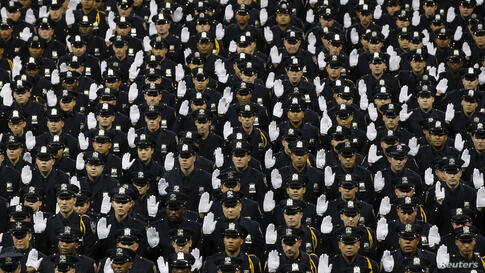 Members of the class of the New York City Police Academy raise hands during their graduation ceremony at Madison Square Garden in New York.
