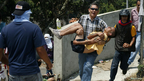 A man carries an injured anti-government protester during a protest against Venezuela's President Nicolas Maduro's government in San Cristobal, Mar. 18, 2014.