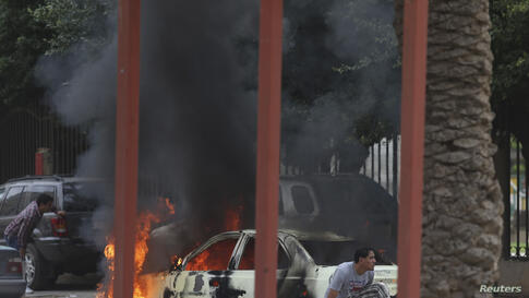 Residents hide near a burning car during clashes between members of Islamist militant group Ansar al-Sharia and a Libyan army special forces unit in the Ras Obeida area in Benghazi.