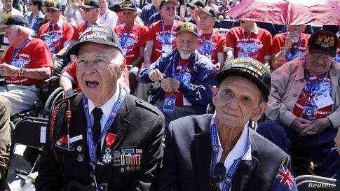 World War II D-Day invasion veterans Herman Zeitchik (L) and Antonio Gimenez (R) are surrounded by other veterans as they attend a ceremony at the National World War II Memorial on the 70th anniversary of the D-Day invasion of Europe, while in Washingt...