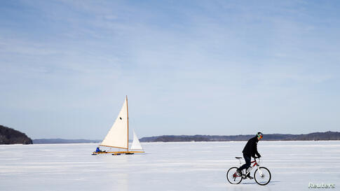 An antique ice boat sails behind a cyclist across the frozen Hudson Raiver near, Astor Point in Barrytown, New York, Mar. 7, 2014. Ice sailors from the Hudson River Ice Yacht Club and other ice sailors on the upper Hudson river are enjoying one of the ...