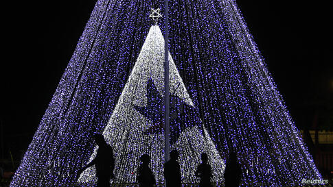 People walk past decorations on a street ahead of Christmas day celebrations in Colombo, Sri Lanka.