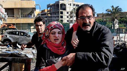 A Lebanese man helps an injured woman, as they pass the site of an explosion, near the Kuwaiti Embassy and Iran's cultural center, in the suburb of Beir Hassan, Beirut, Lebanon. The bombing in a Shi'ite district in southern Beirut killed at least six p...