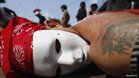 A masked flagellant lies prostrate on the ground as he prays outside a chapel during a Maundy ritual by penitents to atone for sins in Angeles, Pampanga north of Manila.