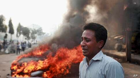 A Bangladeshi man cries after his vehicle was set on fire by Islamist party Jamaat-e-Islami activists during violent protests in Dhaka that followed the execution of their JI party leader Abdul Quader Mollah Thursday.