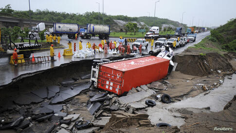 Emergency responders stand near an overturned truck after a road was washed away by floodwaters in Boca del Rio, on the outskirts of Veracruz, Mexico, June 7, 2014.