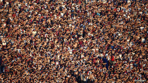 San Lorenzo's fans use their hands to block the sun during the Argentine First Division soccer match against Estudiantes in Buenos Aires, Argentina, Dec. 1, 2013.
