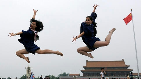 Graduates jump as they pose for photographs in front of the Tiananmen Gate and the giant portrait of late Chinese Chairman Mao Zedong, on the Tiananmen Square in Beijing, June 19, 2014.