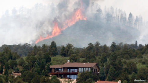 Flames explode near houses in a mountain subdivision, west of Colorado Springs.