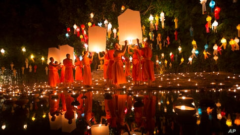 Buddhist monks prepare to release lanterns after a blessing ceremony during the Loy Krathong Festival at a temple in Chiang Mai, Thailand, Nov. 17, 2013.