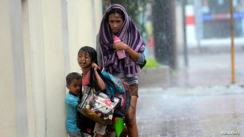 A mother takes refuge with her children as Typhoon Haiyan hits Cebu city, central Philippines.