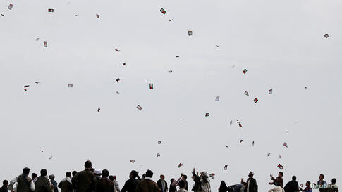 Supporters of Afghan presidential candidate Ashraf Ghani Ahmadzai try to catch leaflets during an election campaign in Kunduz province, northern Afghanistan.