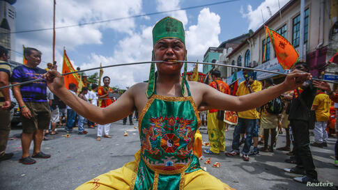 A Chinese devotee, who has his cheeks pierced with a skewer, sits on a chair before marching around Chinatown during the Guan Ping Festival in Kuala Lumpur, Malaysia. The festival, held in celebration to mark the birthday of Chinese deity Guan Ping, is...