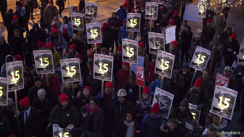Demonstrators stage a rally after a long march from Sea-Tac to raise the hourly minimum wage to $15 for fast-food workers at City Hall in Seattle, Washington, Dec. 5, 2013.