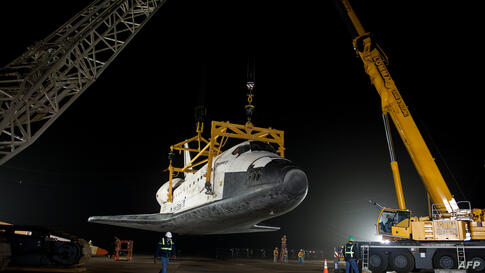 The space shuttle Discovery is suspended from a sling held by two cranes after the NASA 747 Shuttle Carrier Aircraft was pushed back from underneath at Washington Dulles International Airport, in Sterling, Virginia. (NASA/Bill Ingalls)