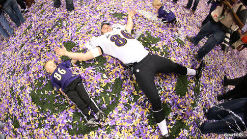Baltimore Ravens tight end Billy Bajema (86) lies in the confetti on the field with his children as he celebrates his team defeating the San Francisco 49ers in the NFL Super Bowl XLVII.