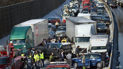 Rescue and fire personnel assist on the scene of a 100-car chain reaction pileup accident on the Pennsylvania Turnpike eastbound in Feasterville. Icy weather conditions contributed to the accident. It is expected to take hours to remove all of the debr...