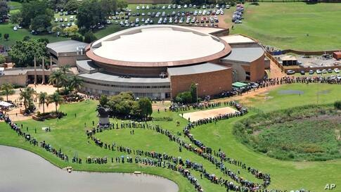 People queue for buses before heading to the Union Building in Pretoria, South Africa, where the body of former South African president Nelson Mandela is lying in state for three days.
