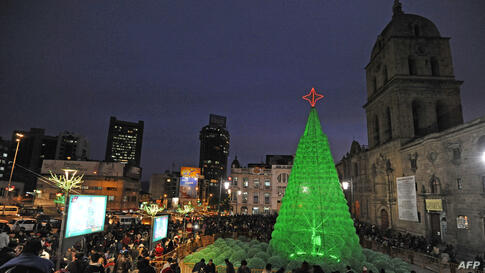 People enjoy the eco-friendly Christmas tree set up at the Basilica de San Francisco explanade in La Paz, Bolivia. The tree of 14 meters high was made with some 50,000 plastic bottles, Dec. 18, 2013.