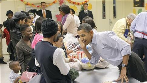 President Barack Obama, right, leans over to listens to hear an unidentified child speak as he helps pack food for Thanksgiving at Martha's Table, a local food pantry in Washington, Wednesday, Nov. 24, 2010. (AP Photo/Pablo Martinez Monsivais)