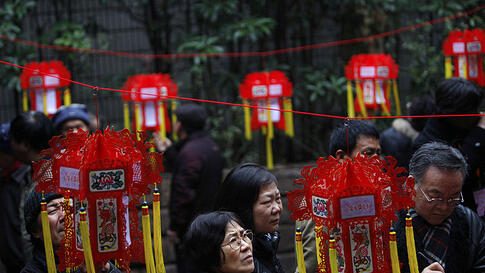 Parents looking for dating opportunities for their children read red lanterns with personal information displayed during a Valentine's Day event in Shanghai, China, February 14, 2012.  (REUTERS)